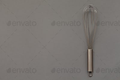 Metal whisk for whipping on a gray background