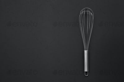 Metal whisk for whipping on a black background