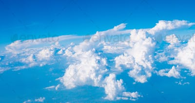 Blue sky with clouds and sun on airplane view
