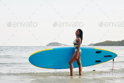 Happy woman with sup surfing board