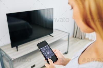 Woman checking tv volume settings