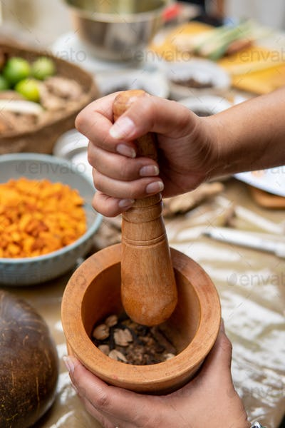 grinding traditional spice ingredient for jamu herbal drink