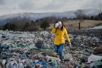 Woman with gas mask walking on landfill, environmental concept