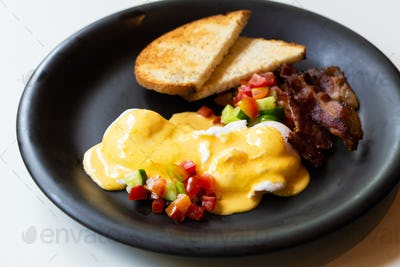 Eggs Benedict - bread ,becon and tomato, poached eggs, and delicious buttery hollandaise sauce