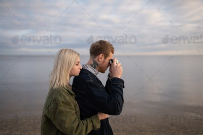 Young couple taking pictures of water in nature