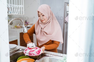 muslim woman washing the dishes
