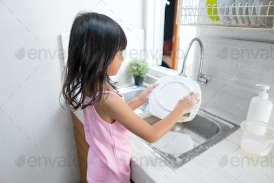 asian little girl wash the dishes