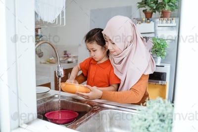 little Girl Help Her Mother In Washing Dishes