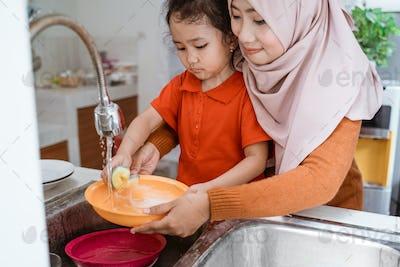 Daughter helping washing dishes
