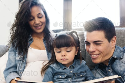 Parents reading a book to their daughter.