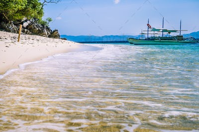 Traditional banca boat in clear water at sandy Beach near El Nido, Philippines