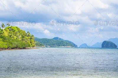Coastline full of rocky islands covered with palm trees in El Nido, Philippines