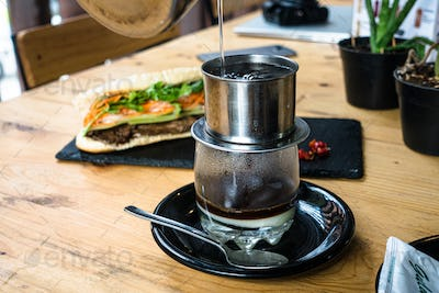 Filtering vietnamese pour over coffee with condensed milk