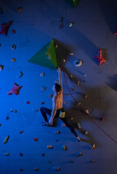 Male boulderer planning climbing route on wall
