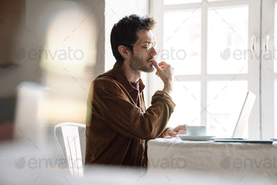 Image of handsome serious man using laptop while sitting