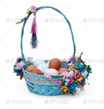 Easter basket with eggs and flower arrangement on a white background