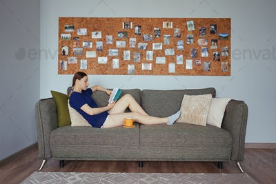 Attractive positive woman reading a book relaxing on the sofa