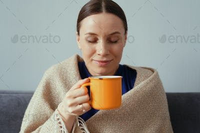 Positive woman enjoying a cup of tea wrapped in a blanket