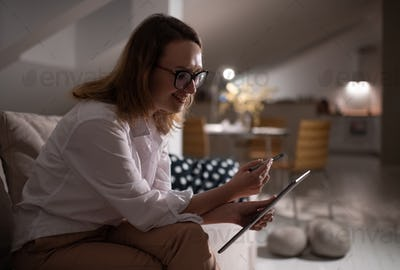 Cheerful woman chatting with friend on tablet at home