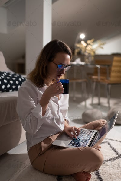 Young busy woman drinking coffee and working on laptop at home