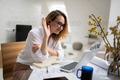 Cheerful businesswoman having online meeting with colleagues