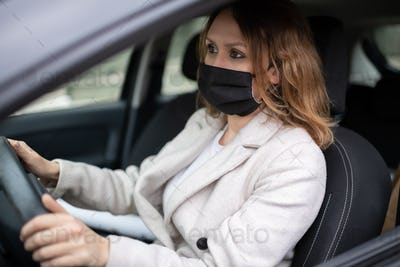 Woman in protective mask driving car