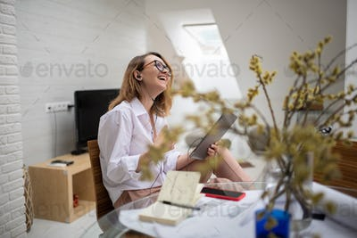 Cheerful businesswoman chatting with friends during online meeting