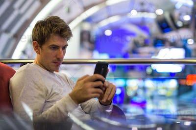 Caucasian man sitting indoors while using mobile phone