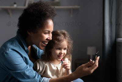 Happy ethnic woman teaching daughter to apply lipstick
