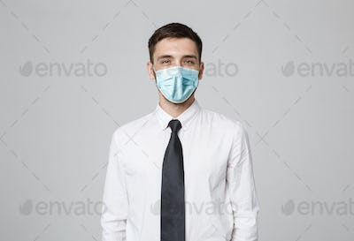 Business Concept - Young successful businessman in face mask posing over dark background. Copy space