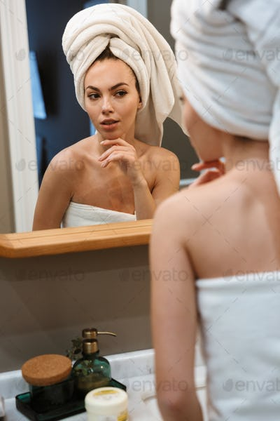 Image of seductive beautiful woman in white towels looking at mirror