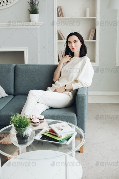 Beautiful young woman on couch in living room