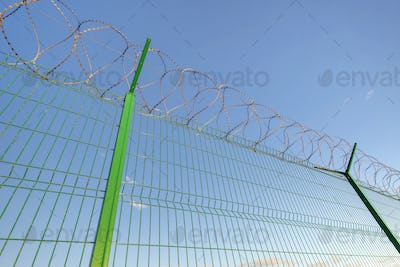 Slatted fence with barbed wire on top.