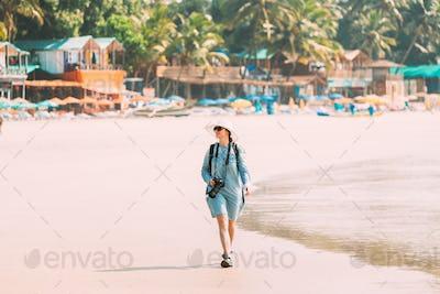 Canacona, Goa, India. Young Caucasian Lady Woman With Camera Walking Along Seashore On Palolem Beach