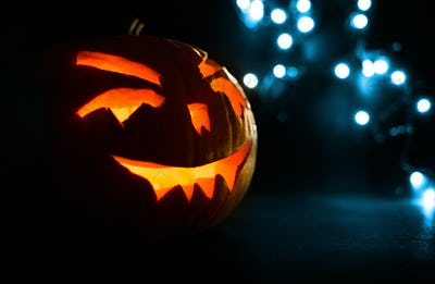 carved face of pumpkin glowing on Halloween on blue bokeh light background