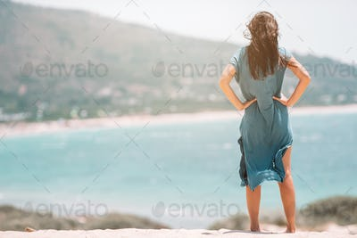 Young beautiful woman on white tropical beach