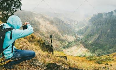 Traveler takes a picture of a gorgeous panorama view of a lush green Xo-xo valley. Santo Antao