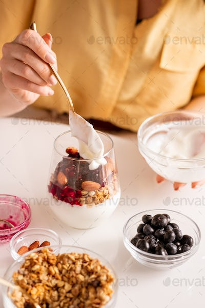 Young female adding fresh sourcream into glass with yoghurt ingredients