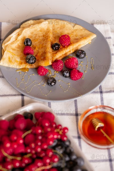 Plate with two folded appetizing pancakes with honey and fresh berries on table