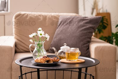 Bunch of white flowers in jug with water, snack on plate and green herbal tea