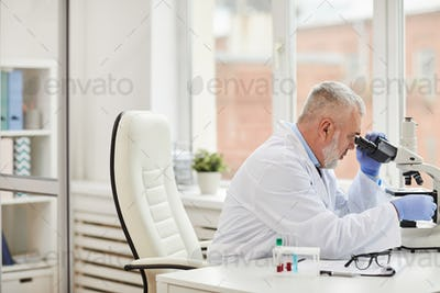 Medical specialist using microscope