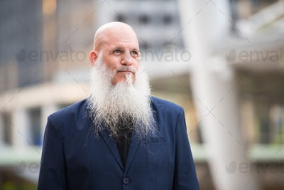 Mature bearded bald businessman thinking in the city outdoors