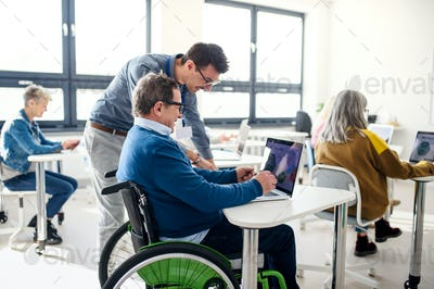Senior man in wheelchair attending computer and technology education class