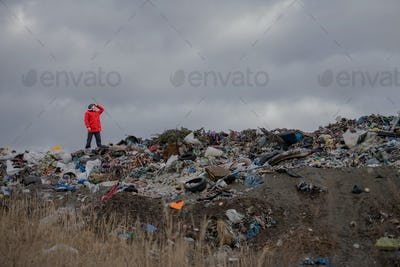 Man standing on landfill, environmental concept. Copy space