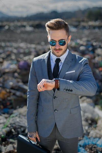 Modern businessman on landfill, consumerism versus pollution concept