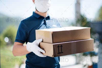 Unrecognizable courier with face mask delivering parcel, corona virus and quarantine concept