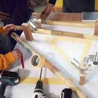 Close Up Of Multi-Cultural Team In Workshop Assembling Hand Built Bamboo Bicycle Frame
