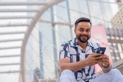 Happy young bearded Indian man with phone sitting in the city outdoors