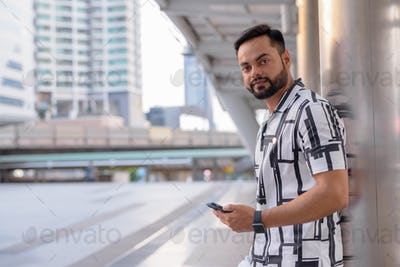 Young bearded Indian man using phone outdoors