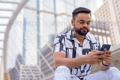 Young bearded Indian man using phone while sitting in the city outdoors